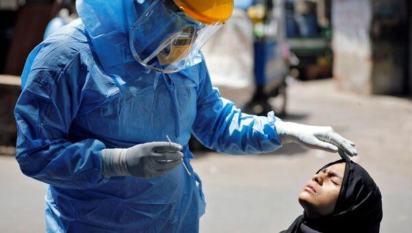 Доктор в защитном костюме тестирует девушку на коронавирус в Ахмедабаде, Индия - Sputnik Ўзбекистон