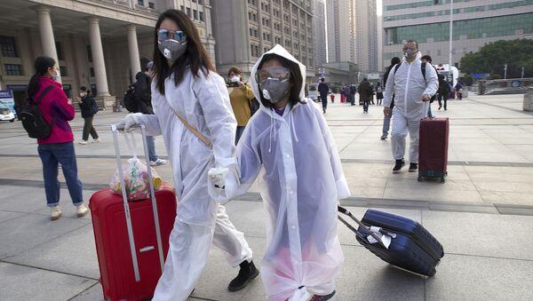 Пассажиры в защитных масках возле вокзала Уханя  - Sputnik Ўзбекистон
