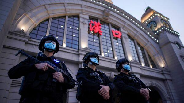 Сотрудники службы безопасности в защитных масках у железнодорожного вокзала Ханькоу в Ухане, Китай - Sputnik Ўзбекистон