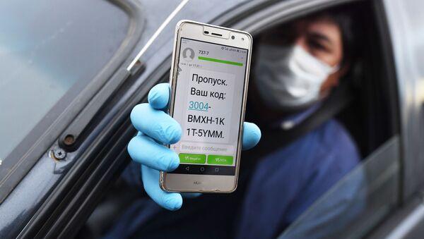 Водитель показывает код своего электронного пропуска на экране смартфона сотруднику дорожно-патрульной службы ГИБДД во время остановки на блокпосту при въезде в Москву - Sputnik Узбекистан