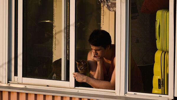 Молодой человек с кошкой на балконе многоквартирного дома в Москве - Sputnik Ўзбекистон