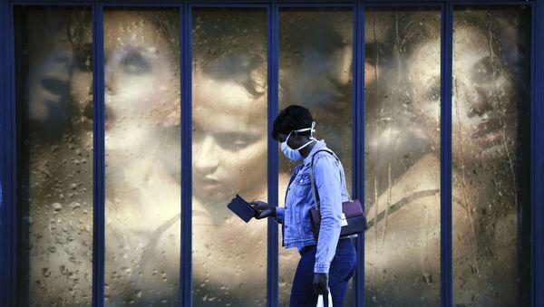 Женщина в медицинской маске на фоне витрины магазина в Париже, Франция - Sputnik Ўзбекистон