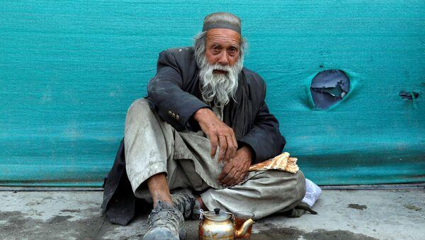 Бездомный мужчина пьет чай в придорожном чайном магазине в Кабуле, Афганистан - Sputnik Ўзбекистон