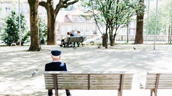 Пожилой мужчина сидит на скамейке в парке - Sputnik Узбекистан