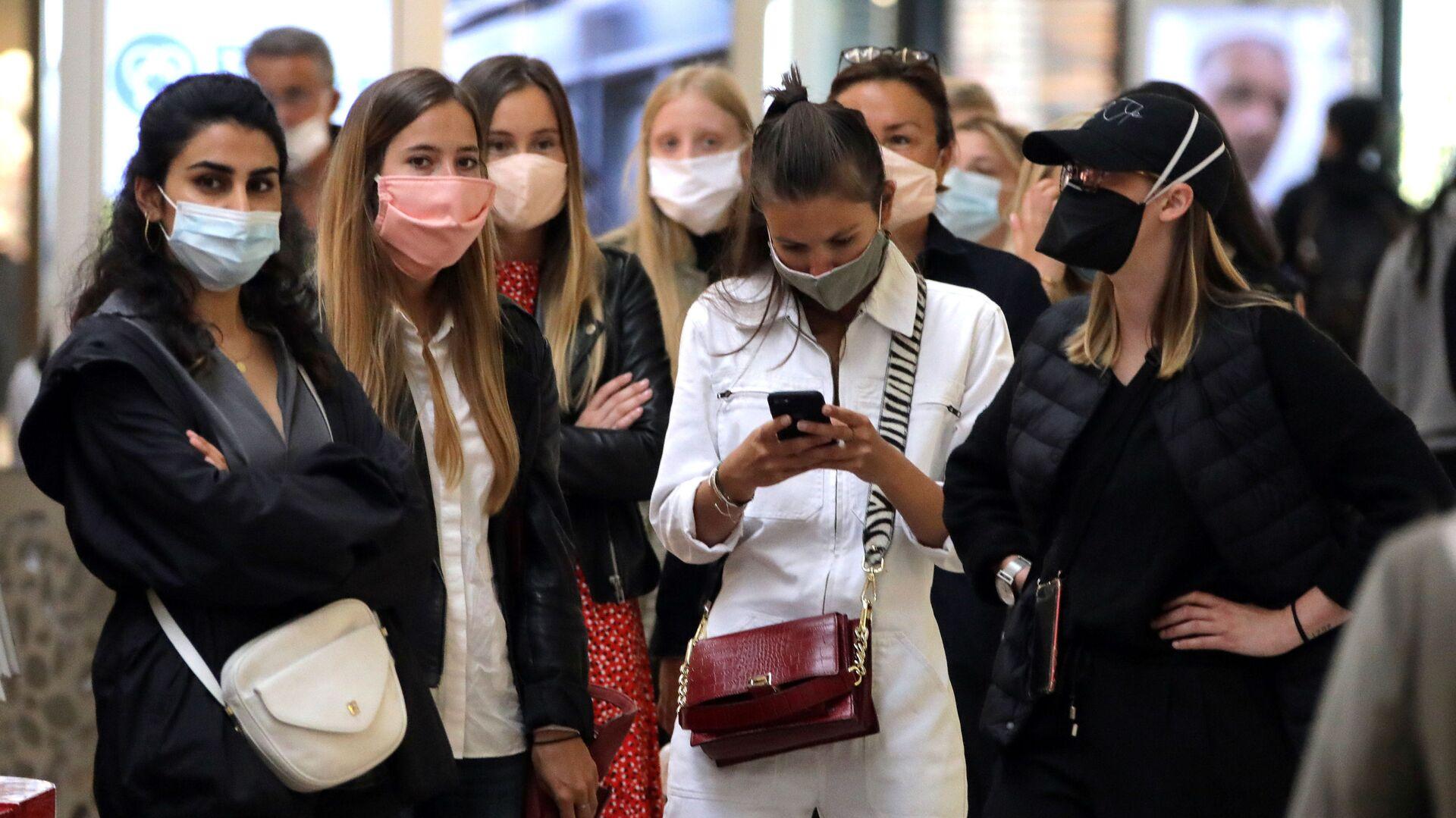 Девушки в масках во время открытия магазина после облегчения карантинных мер во Франции  - Sputnik Узбекистан, 1920, 05.10.2021