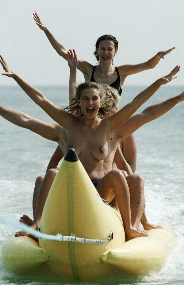 Девушки катаются на надувном банане во время отдыха на черноморском курорте - Sputnik Узбекистан