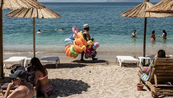 Отдыхающие и продавец игрушек на городском пляже Алимос в пригороде Афин - Sputnik Узбекистан