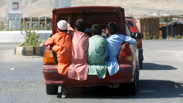 Afganskiye deti yedut v bagajnike avtomobilya v provintsii Lagman, Afganistan - Sputnik Oʻzbekiston