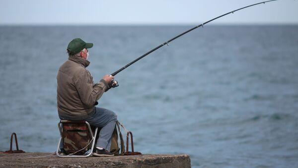 Рыбак на набережной Алушты после отмены режима самоизоляции в Крыму - Sputnik Ўзбекистон