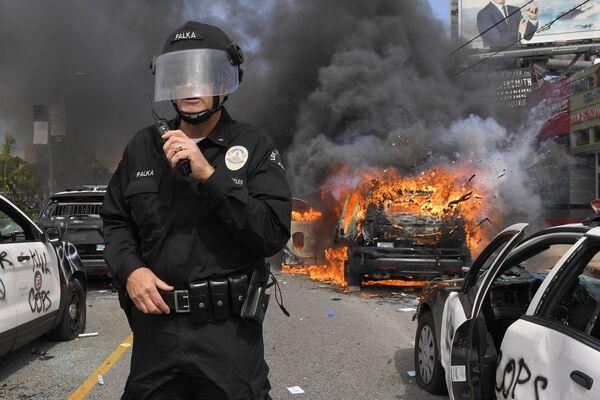 Полицейский Лос-Анджелеса на фоне горящей машины во время протестов  - Sputnik Узбекистан