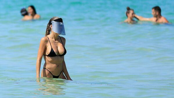 Женщина с защитным экраном на лице на пляже в Майами-Бич, Флорида - Sputnik Ўзбекистон