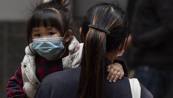 Девочка в защитной маске на руках у матери на одной из улиц в Гонконге - Sputnik Узбекистан