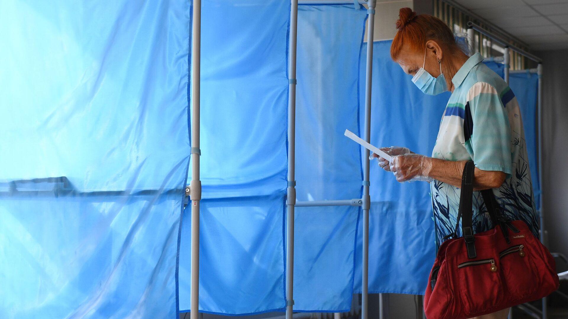 Женщина принимает участие в голосовании по внесению поправок в Конституцию РФ на избирательном участке №1503 в Новосибирске - Sputnik Узбекистан, 1920, 20.09.2021