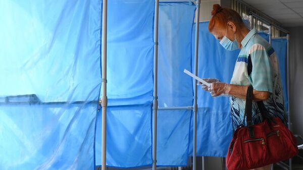Женщина принимает участие в голосовании по внесению поправок в Конституцию РФ на избирательном участке №1503 в Новосибирске - Sputnik Узбекистан