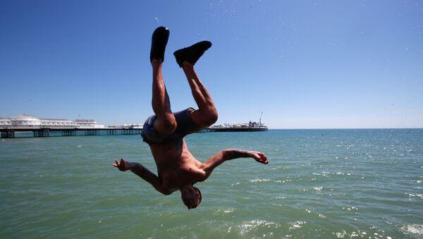 Мужчина прыгает в воду на пляже в Брайтоне, Великобритания - Sputnik Ўзбекистон