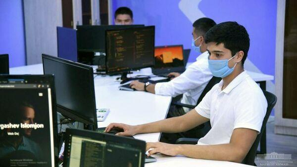 Молодые люди работают за компьютерами - Sputnik Узбекистан