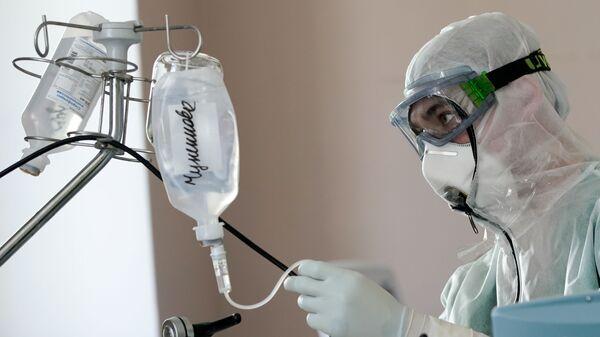 Медицинский сотрудник устанавливает капельницу в стационаре для больных с коронавирусной инфекцией - Sputnik Узбекистан