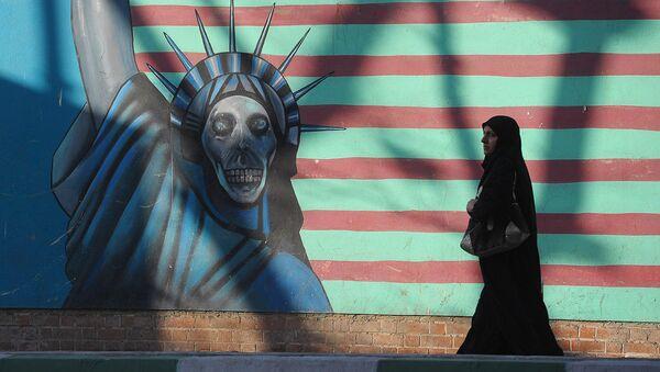 Женщина идет вдоль стены здания бывшего посольства США в Тегеране - Sputnik Ўзбекистон