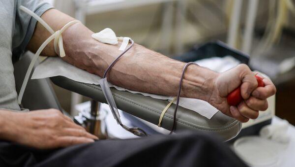 Донор во время процедуры сдачи крови на станции переливания крови - Sputnik Узбекистан