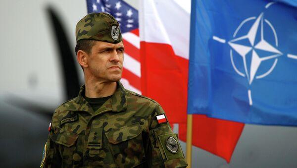Польский военнослужащий на фоне флага NATO - Sputnik Ўзбекистон
