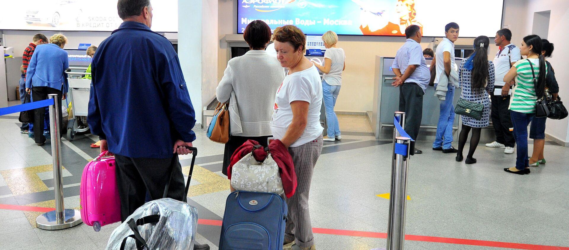 Пассажиры у стойки регистрации билетов в международном аэропорту - Sputnik Узбекистан, 1920, 25.12.2020