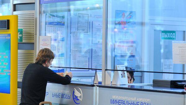 Молодой человек покупает билет в кассе международного аэропорта - Sputnik Узбекистан