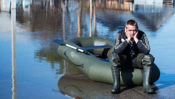 Местный житель рядом с жилыми домами, затопленными в результате паводка - Sputnik Узбекистан