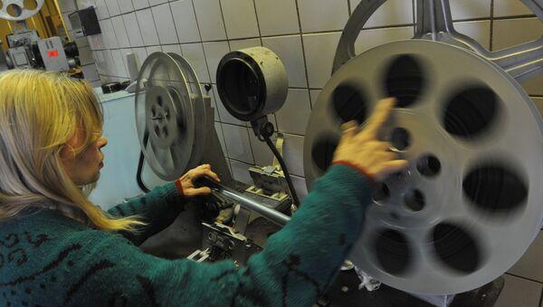 Kinoteatr xodimi kinolentani proyektorga oʻrnatayapti - Sputnik Oʻzbekiston