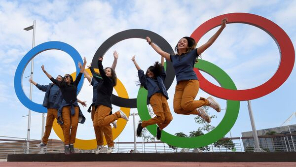 Люди на фоне олимпийских колец в Рио-де-Жанейро - Sputnik Ўзбекистон