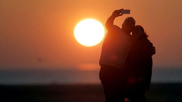 Молодые люди делают селфи на фоне заката - Sputnik Узбекистан
