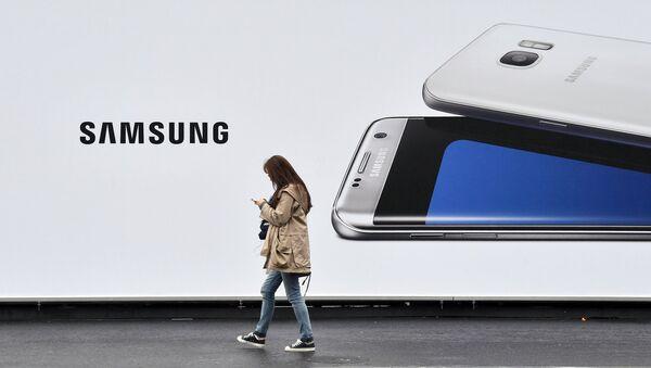 Jenщina proxodit mimo stenda s izobrajeniyem telefona Samsung - Sputnik Oʻzbekiston