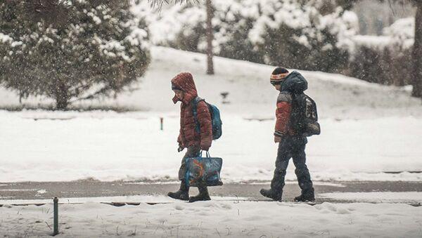 Школьники идут во время снегопада в школу - Sputnik Узбекистан