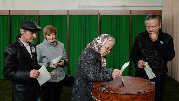 Женщина голосует на избирательном участке в Ташкенте во время выборов президента Узбекистана - Sputnik Узбекистан