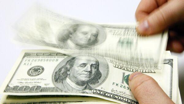 Мужчина пересчитывает доллары США, фото из архива - Sputnik Ўзбекистон