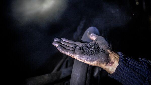 Шахтер показывает уголь. Архивное фото - Sputnik Ўзбекистон
