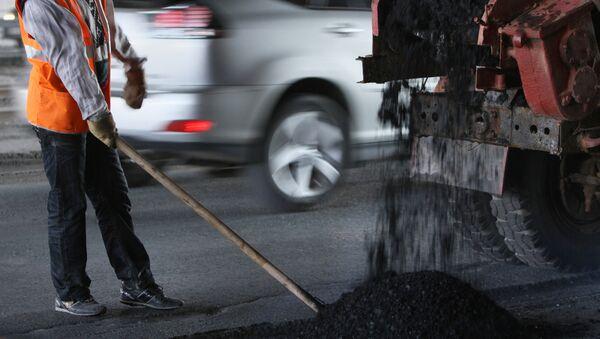 Работник дорожного хозяйства укладывает новый асфальт - Sputnik Ўзбекистон