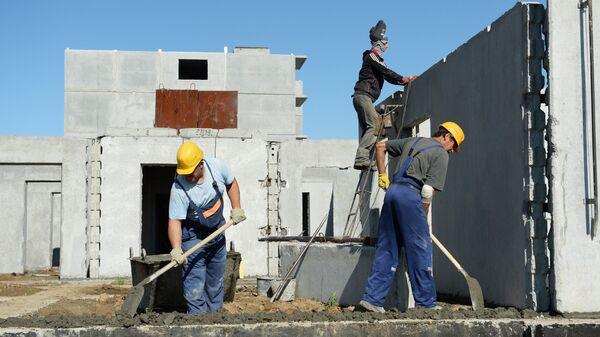 Строители осуществляют монтаж стеновых панелей цокольного этажа многоквартирного жилого дома - Sputnik Ўзбекистон