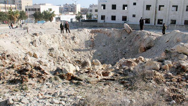 Воронка образованная в результате авиаудара в городе Идлиб в Сирии - Sputnik Ўзбекистон