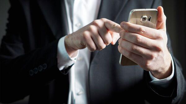 Мобильный телефон в руке - Sputnik Узбекистан
