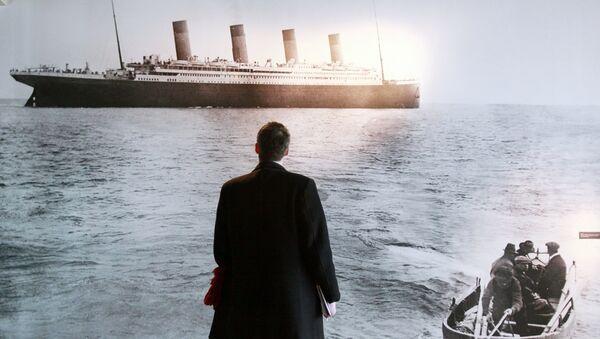 Мужчина смотрит на фотографию, на которой изображен Титаник - Sputnik Узбекистан