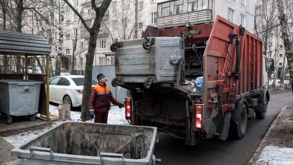 Сотрудник коммунальных служб выгружает мусор - Sputnik Ўзбекистон