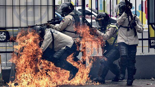 Бутылка с зажигательной смесью попала в группу полицейских во время акции против президента Николаса Мадуро в Каракасе - Sputnik Узбекистан