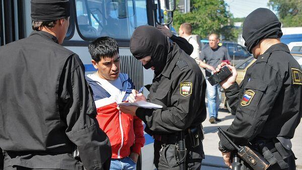 Сотрудник ОМОН регистрируют задержанного во время рейда на одном из рынков - Sputnik Узбекистан