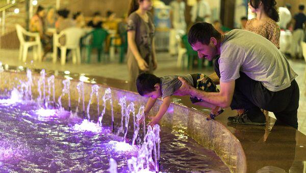 Mujchina igrayet u fontana s rebenkom, arxivnoye foto - Sputnik Oʻzbekiston