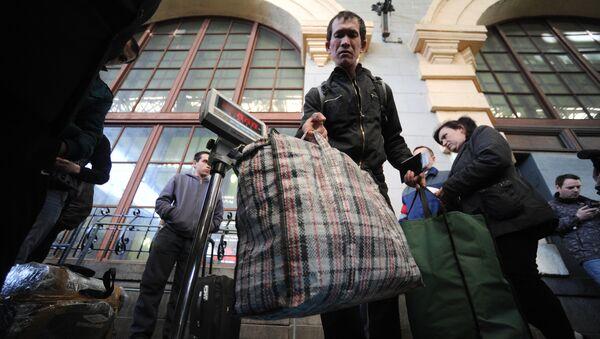 Пассажиры поезда Москва – Душанбе взвешивают багаж на перроне Казанского вокзала - Sputnik Узбекистан