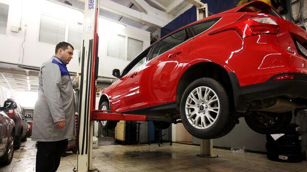 Сотрудник сервисного центра осуществляет технический осмотр транспортного средства - Sputnik Ўзбекистон