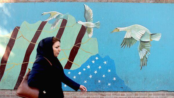 Женщина проходит мимо граффити с изображением флага США в Тегеране - Sputnik Узбекистан