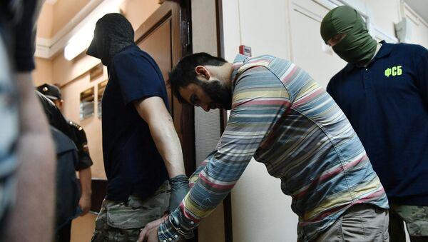 Сотрудники правоохранительных органов выводят одного из подозреваемых в подготовке взрывов в Москве - Sputnik Узбекистан