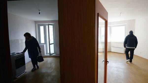 Мужчина и женщина осматривают свою квартиру в новом жилом доме - Sputnik Ўзбекистон