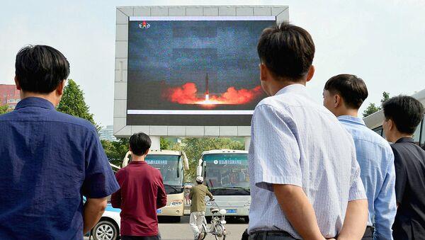 Северные корейцы наблюдают за новостным сообщением, показывающим запуск ракеты средней дальности - Sputnik Ўзбекистон